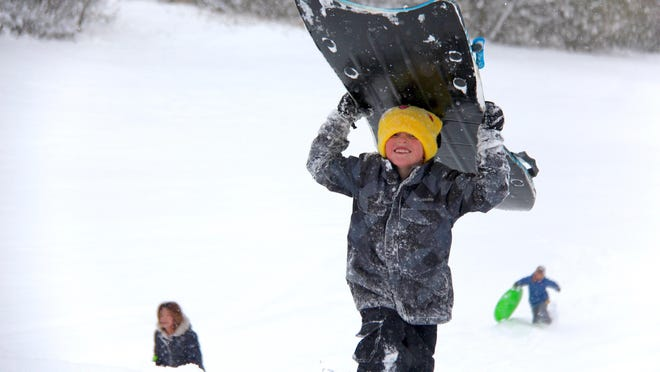 """Ryker Smith treks up the sledding hill at Van Raalte Park after going for a ride on Tuesday, Nov. 12, 2019. The recently released Farmers' Almanac forecasts the Great Lakes and Midwest are """"in for a cold winter, with normal to below-normal temperatures."""
