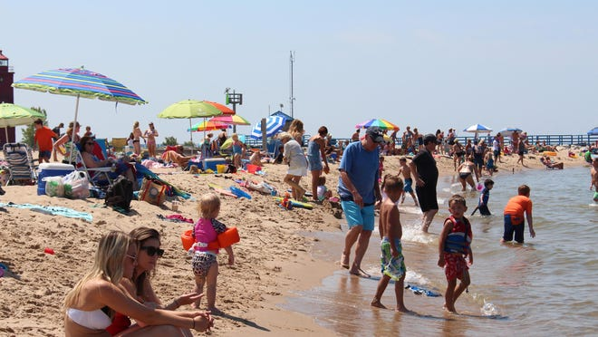 Families enjoy a summer day at Holland State Park in this 2016 file photo. Proposal 1 will alter how the state uses funds for state park and natural resource conservation, committing oil and gas royalties to land preservation, water sources and parks and lifts the cap on Michigan Natural Resources Trust Fund.