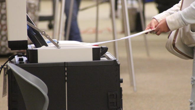 A voter feeds her ballot into the voting machine Tuesday, Nov. 3, at Noordeloos Christian Reformed Church.