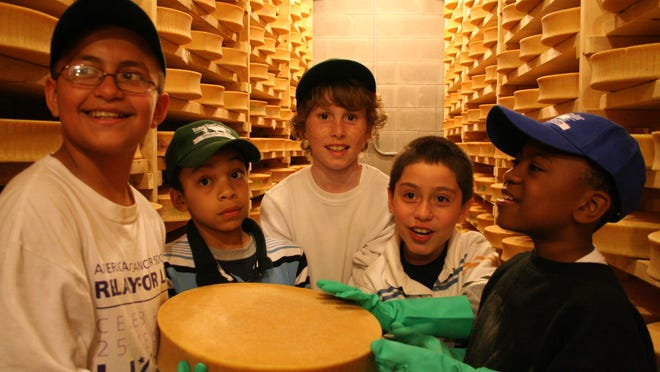 Fifth graders from De La Salle School in Freeport, Long Island show off a wheel of the Spring Brook Farm Tarentaise cheese, which they helped to turn and wash as part of their weeklong Farms for City Kids program visit to the Reading farm in 2010.  The farm's Ashbrook cheese won an award in the 2021 Good Food Awards, sponsored by the San Francisco-based Good Food Foundation.