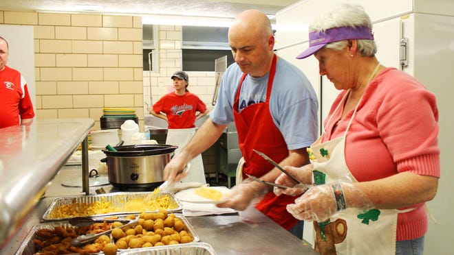 Jim Schreyer and Marian Button dish up goodies at the Lenten Fish Fry at St. Therese Little Flower Church in Mount Airy.