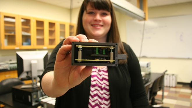 Clemson University doctoral student Kayla Gainey with the glucose meter that has attracted investors interested in launching a start-up company.