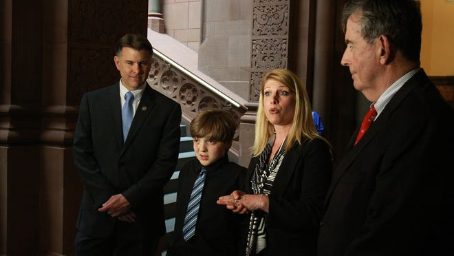 Frankie Flora, 10, a victim of a dog attack, and his mother Maria Flora, spent Monday in Albany, lobbying to ensure dog owners pay victims' medical costs. Sen. Terry Gipson, D-Rhinebeck, (left) and Sen. Neil Breslin, D-Delmar, Albany County are sponsoring a bill which would hold a dog owner liable when their pet bites someone and causes injury the first time it happens.