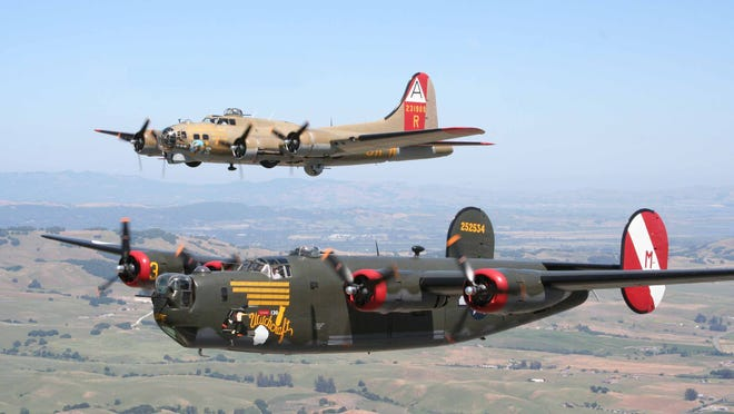 """A B-24 Liberator flies in the foreground with a B-17 """"Flying Fortress"""" in the background. The vintage aircraft will visit Dutchess next week."""