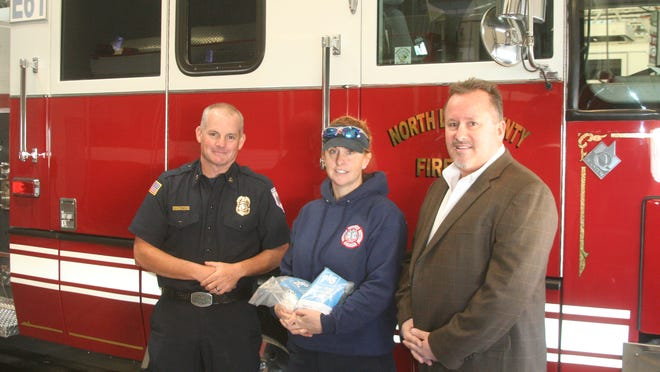 North Lyon County Fire Protection District chief Scott Huntley and firefighter Kelli Cartwright thank plant manager Jared Kerney of Johns Manville for its $1,000 donation.