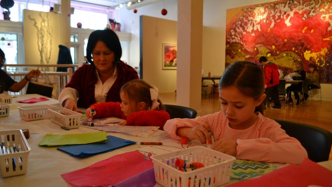 """Suzanne Demech helps her daughters Jacqueline, 3, and Lila Grace, 8, decorate the """"fins"""" of fish for a community art project."""