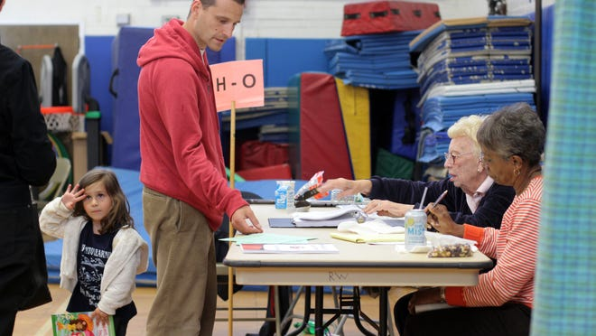 A voter brings his daughter to vote in the 2012 White Plains school elections, at the Ridgeway School polling station.