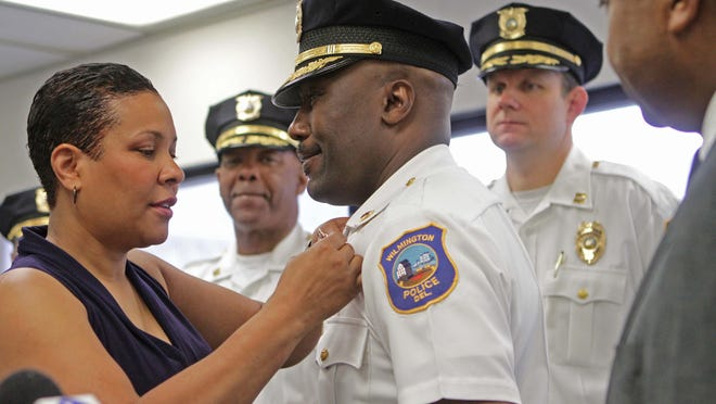 Simone Cummings pins her husband, Bobby Cummings, with his new chief of police badge for the City of Wilmington on Friday.