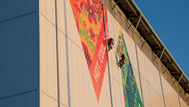Workers attach banners to the Fisht Olympic Stadium in the Olympic Park prior to the 2014 Sochi Winter Olympics. This is where the opening ceremony will be held and officials are concerned about protests.