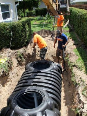 Workers from Reliable Septic and Services install a hybrid septic system that uses a pump to pipe wastewater from existing septic tanks to Vero Beach's sewer plant. The drain field is left in, so it can be used during power outages.