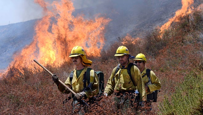 Firefighters battle the Blue Cut Fire along Swarthout Canyon Road in the Cajon Pass, north of San Bernardino, Calif., on Aug. 16, 2016.