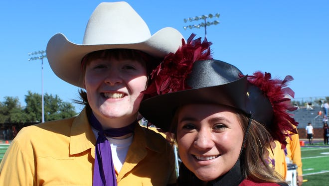 Audrey Haddox, a Hardin-Simmons junior clarinetist, left, and Symphony Munoz, who plays the flute for McMurry, were pals Saturday at the rivalry football game between their two schools.