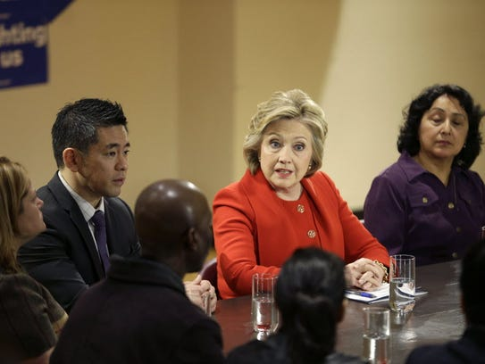 Hillary Clinton talks with local politicians and immigrant