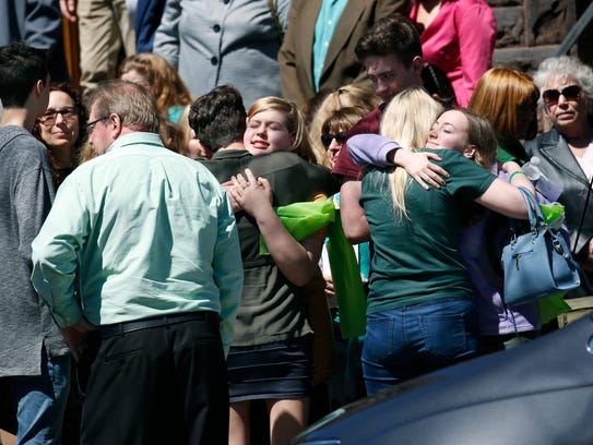 Friends and family of Michael Lynch hug after the funeral