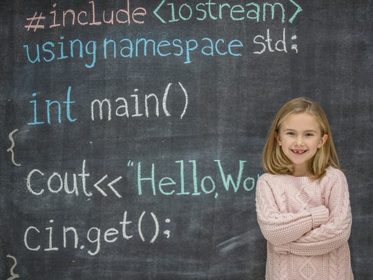 A young girl is learning how to code and program in