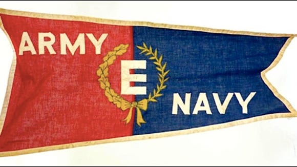 "The Army-Navy ""E"" Award Flag was flown over plants receiving that excellence in production award"