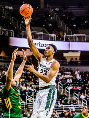 Deyonta Davis ,right, of MSU lays the ball up and in over a Northern Michigan defender during their game Wednesday.