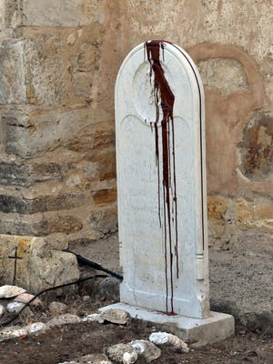 Brown paint mars the tombstone of a man known as Old Gabriel at the Carmel Mission where the remains of Father Junipero Serra, the recently canonized missionary are buried, Sunday, Sept. 27, 2015 in Carmel, Calif. Vandals defaced a statue of Father Junipero Serra at the Carmel Mission, where the remains of the recently canonized missionary are buried, police said Sunday. (Jay Dunn/The Californian via AP)