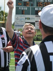 Tom Monaghan flips the coin before the start of the first home football game in Ave Maria University history, in 2011, at Palmetto Ridge High School in Naples.