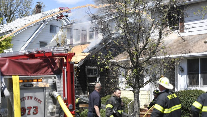 Firefighters from Totowa, Paterson, West Paterson and other nearby towns work on a fire that engulfed one home and spread to the neighboring home at on Boyle Avenue in Totowa on Tuesday.
