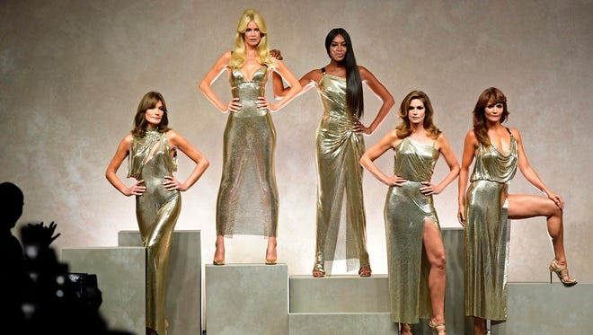 Golden girls: Carla Bruni, Claudia Schiffer, Naomi Campbell, Cindy Crawford and Helena Christensen pose at the end of the Versace show on Sept. 22.