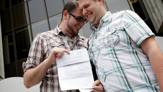 Richard Becherer, 26, left, and Michael Johnson, 23, both from Memphis, Mich., hold their marriage license on Friday, June 26, 2015, at Macomb County Clerk in Mt. Clemens. The U.S. Supreme Court legalized same-sex marriage today.
