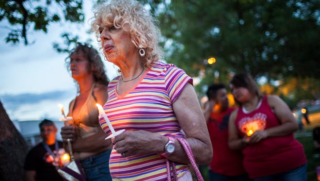 In this May 29, 2014, photo, Denee Mallon, center, joins a candlelight vigil organized by Albuquerque Pride.