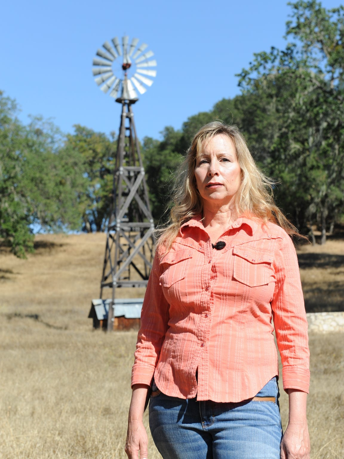 Kim Routh stands near a windmill on her ranch in San