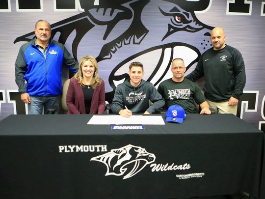 Plymouth senior baseball player Kyle Aniol, along with family and coaches, celebrates signing to play at Madonna University.