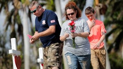 Bryan and Amber Gruzenksy place flowers on crosses