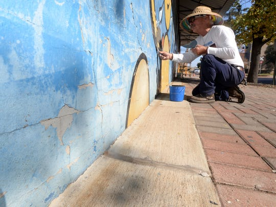 Local artist Chris Opp is re-painting the old Sci-Port mural on the building at Milam and Commerce Streets.