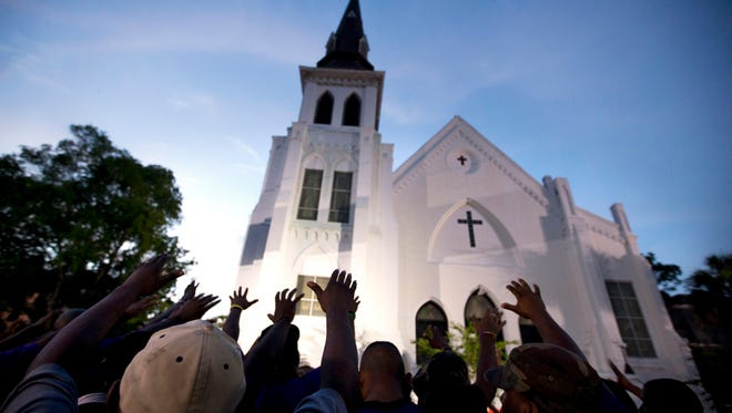 The men of Omega Psi Phi Fraternity lead a crowd of people in prayer outside Emanuel AME Church in June 2015 after a memorial service for nine Black worshippers killed in a racist attack in Charleston.