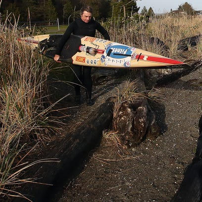 Steve Rhoades carries his paddleboard to the shore