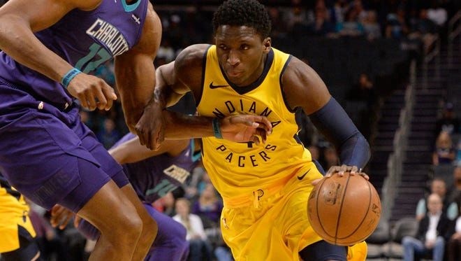 Indiana Pacers guard Victor Oladipo (4) drives past Charlotte Hornets forward center Dwight Howard (12) during the first half at the Spectrum Center.