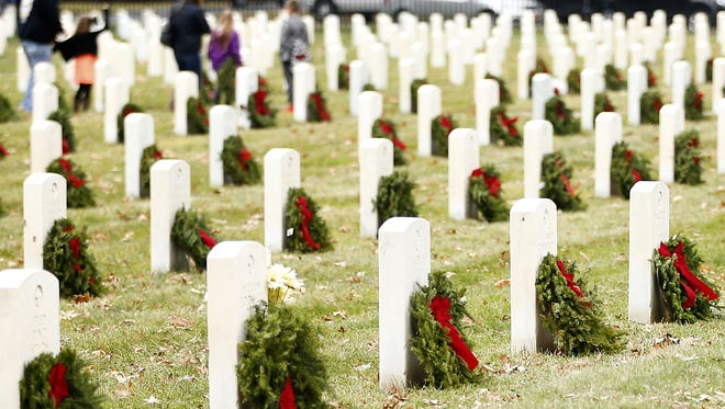 More than 1,200 wreaths adorn Woodlawn National Cemetery grave sites as part of Wreaths Across America.