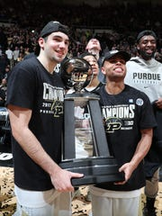 Purdue guards Dakota Mathias (31) and P.J. Thompson (11) hold the Big Ten championship trophy.