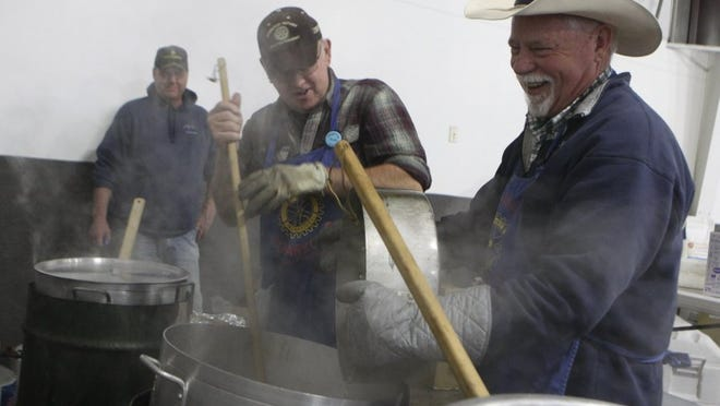 Vick Lohuis (center) and Dennis Patterson (right) stir pots of clam chowder while fellow Anderson Rotary Club member Jeff Hall (left) looks on at the crab feed in 2015. Club members were getting ready for their annual crab feed at the Shasta District Fair grounds.
