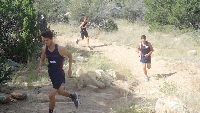 Junior Jonathan Chacon left, and sophomore teammate Daniel Perez, center, ran well for the Deming Wildcats at the Cobre Indians Invitational Cross Country Meet held Saturday, Sept. 16 in Bayard, NM