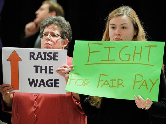 Fran Sobczak, left, and Alexandria Winslow, right, hold signs as they listen to Gov. Andrew Cuomo deliver a speech.