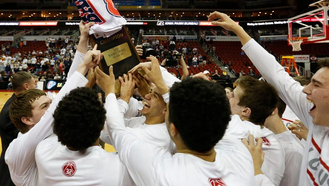 Members of the North Scott team raise their trophy Saturday after the Class 4-A state boys' basketball championship game at Wells Fargo Arena. North Scott defeated Pleasant Valley 44-36 for its first championship.