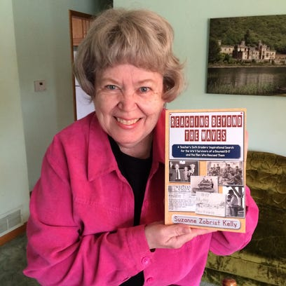 """Suzanne Kelly poses with a copy of her new book, """"Reaching"""