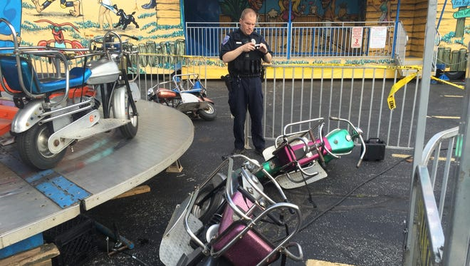 A police officer stands by a ride that malfunctioned Tuesday night, injuring two children.