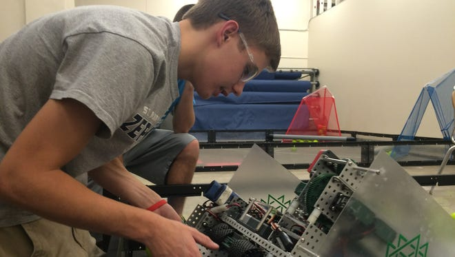 Greg Gurta, a senior at St. Mary Catholic High School, adjusts his team's robot in the newly expanded Technology Center.