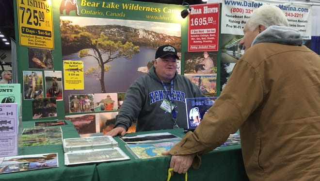 Outfitter Bill Drane talks with a customer at the Boat, RV, and Sportshow.