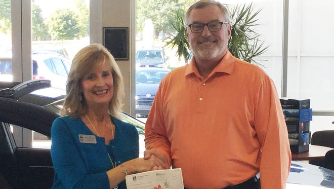 Karen Mitchell, College Foundation executive director, receives a check for $10,000 from Ron Hibbard.