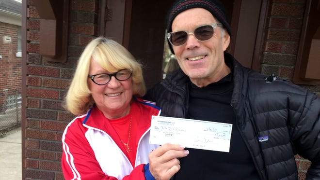 Providing cash to keep alive Detroit's 48th-annual New Year's Eve run runs, Larry John -- a preservation developer in the city's historic Woodbridge district -- hands a $5,000 check on Tuesday, Nov. 21, 2017, from his company Woodbridge Mgt. to Jeanne Bocci of Grosse Pointe Park, founder and race director of the event on Belle Isle.