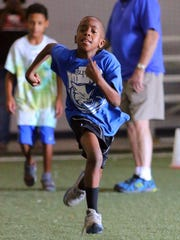 Jaylen Donald runs the 40-yard dash during Murfreesboro Football League evaulations held at Oakland High School's indoor practice facility.