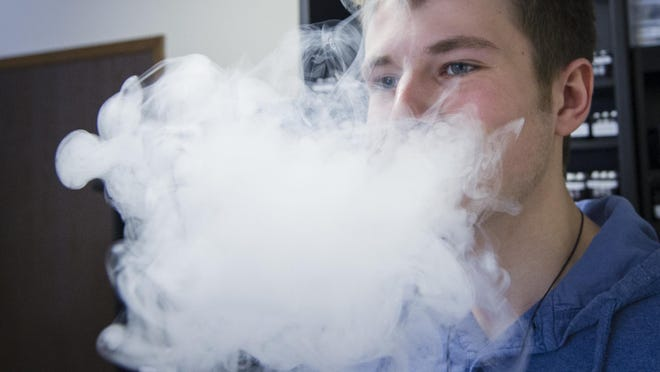 A cloud of vapor from a vaporizer fills the air as store clerk Josh Faust vapes. Main Street Vapor Store opened for business in August of 2013.