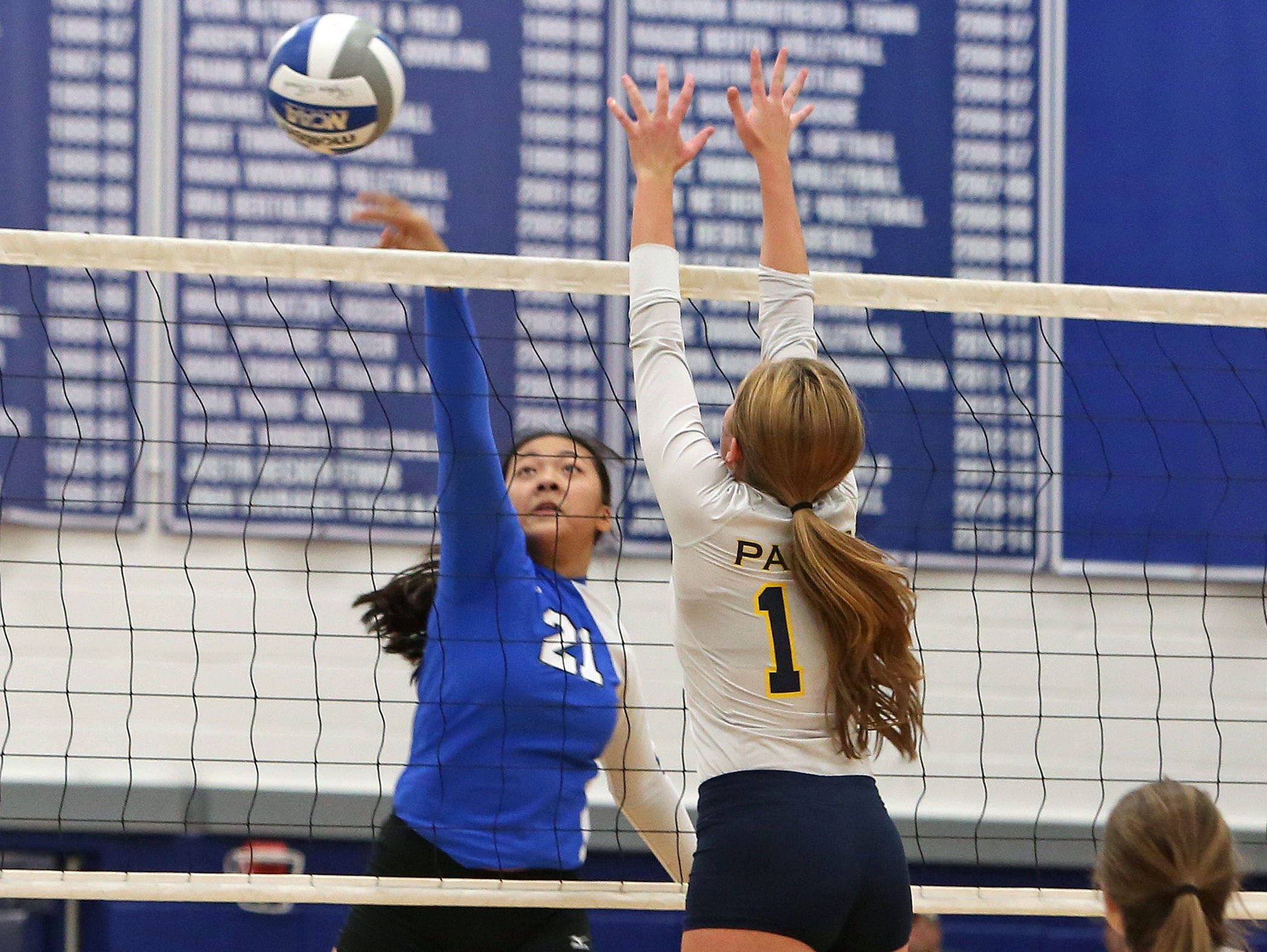 From left, Hen Hud's Kristin Loh (21) gets a shot by Walter Panas' Shauna O'Flaherty (11) during volleyball action at Hendrick Hudson High School in Montrose Oct. 8, 2015. Panas swept the host 3-0.