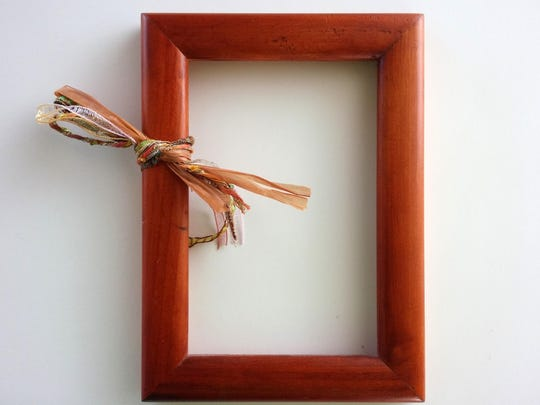 Fold strand of yarn or ribbon in half, and tie once around the frame. Repeat until frame is covered and creates a wreath.